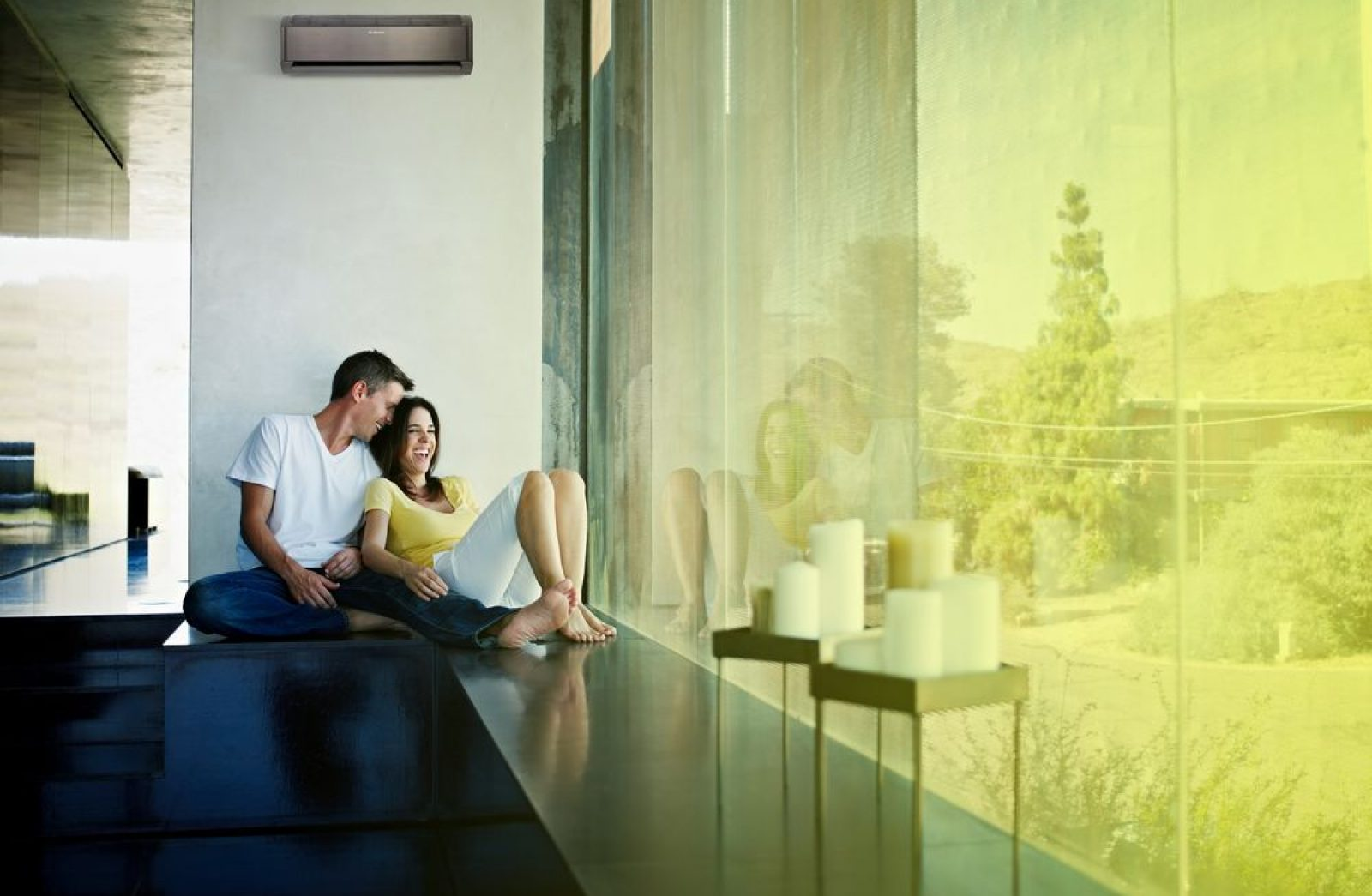 Husband and wife sitting near window of home laughing